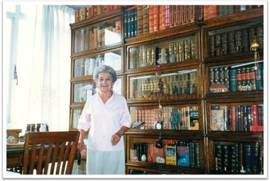 Carmen Castañeda Olea frente biblioteca de su padre Dr. Gonzalo Castañeda Escobar